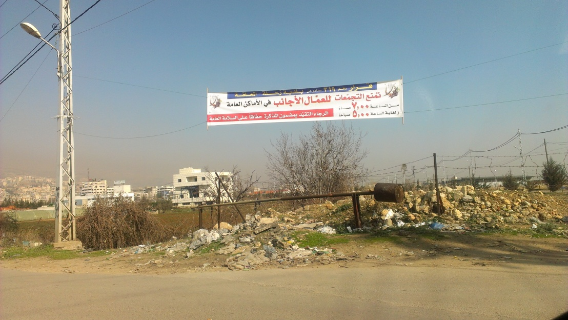 """[Banner reads, among other things: """"Gatherings of foreign workers are forbidden in public spaces. Image by author.]"""